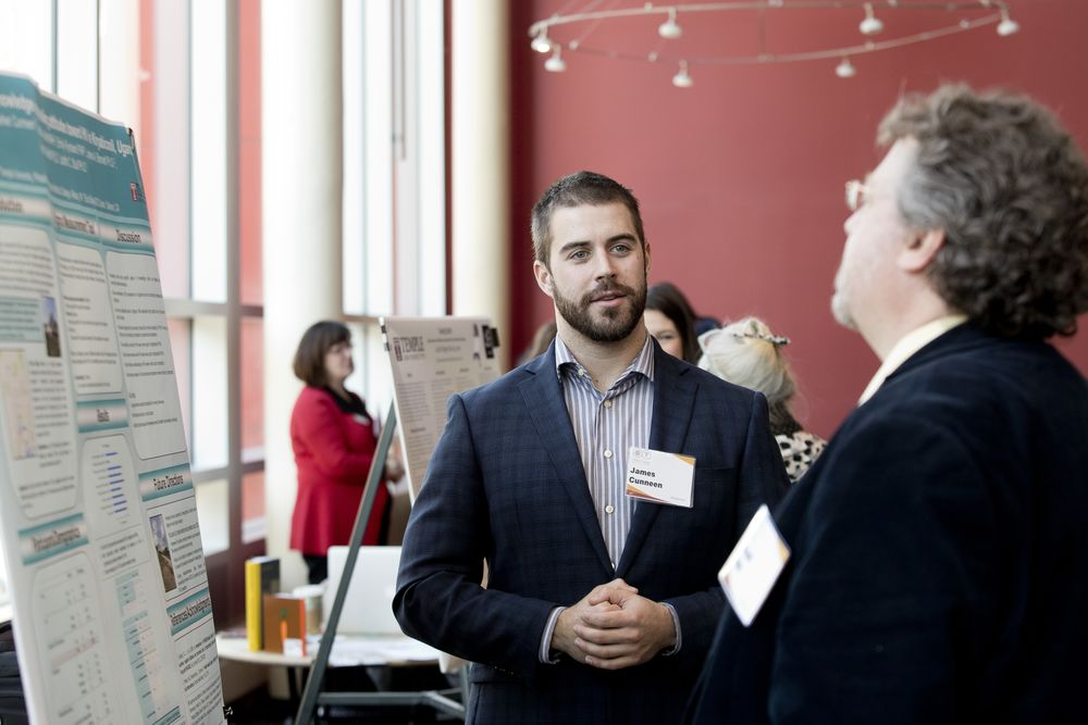 A male student wearing a blazer is in conversation during a professional event.
