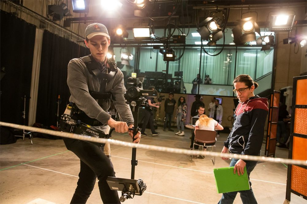 A student in a film studio carefully handles a camera while another student looks on.