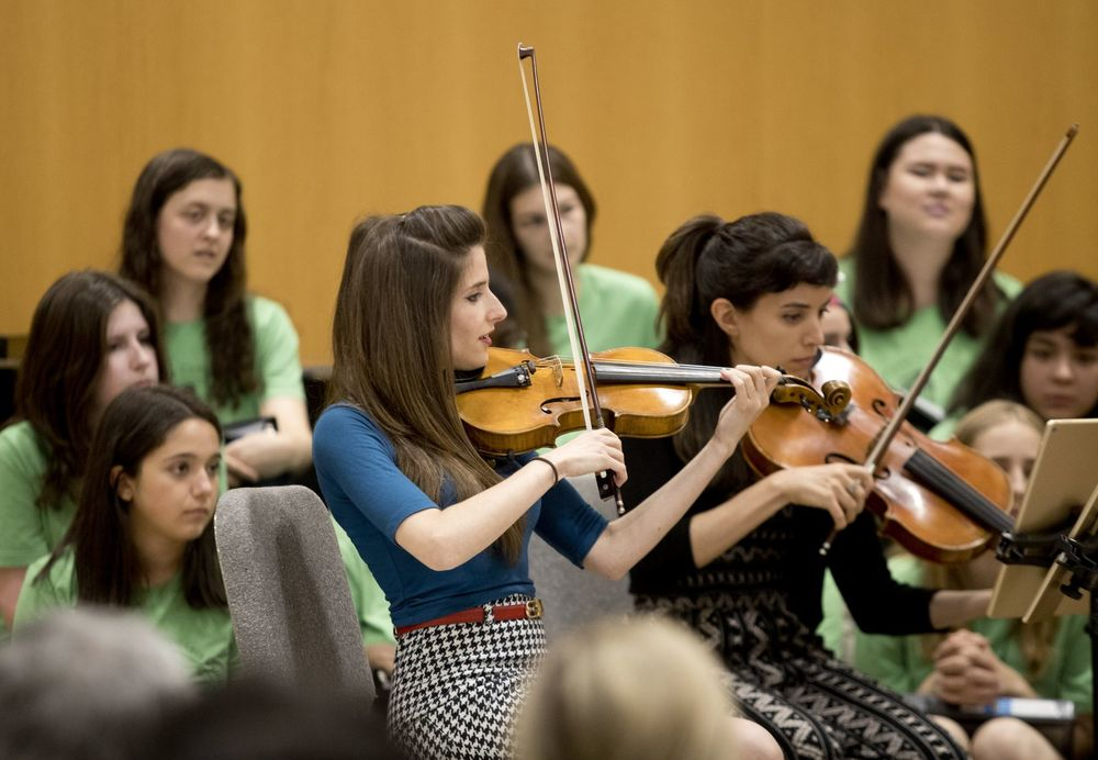 Two women play violin for students.
