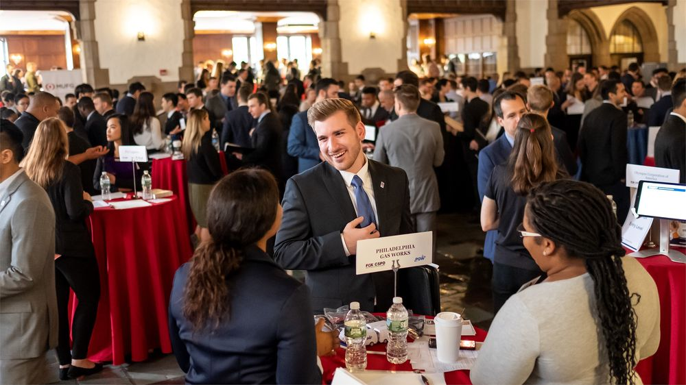 A student socializes at a networking event in a room full of people.
