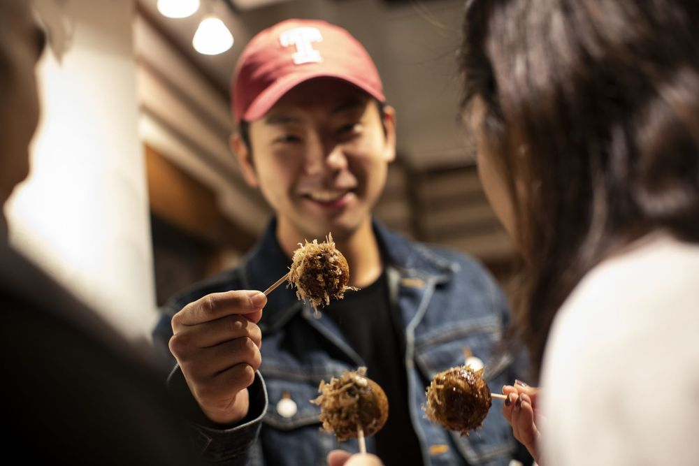 A smiling student wearing a red Temple University hat holds up a dumpling on a toothpick.