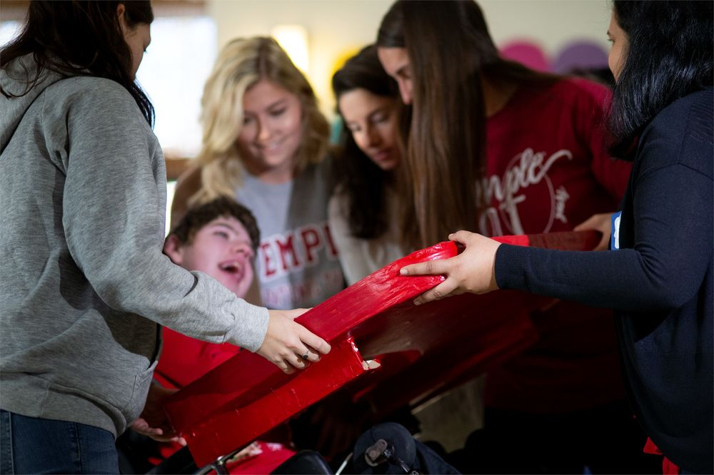 College of Public Health Occupational Therapy students help fit a young child with adaptive equipment.