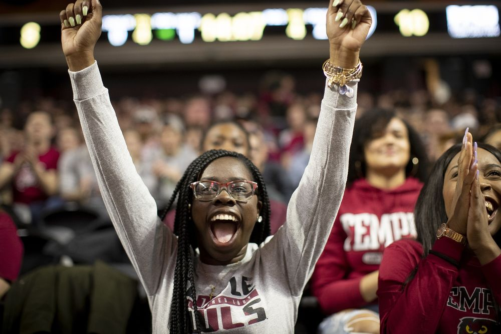 Female student in the crowd at a Temple basketball game has her arms outstretched over her head in glee.