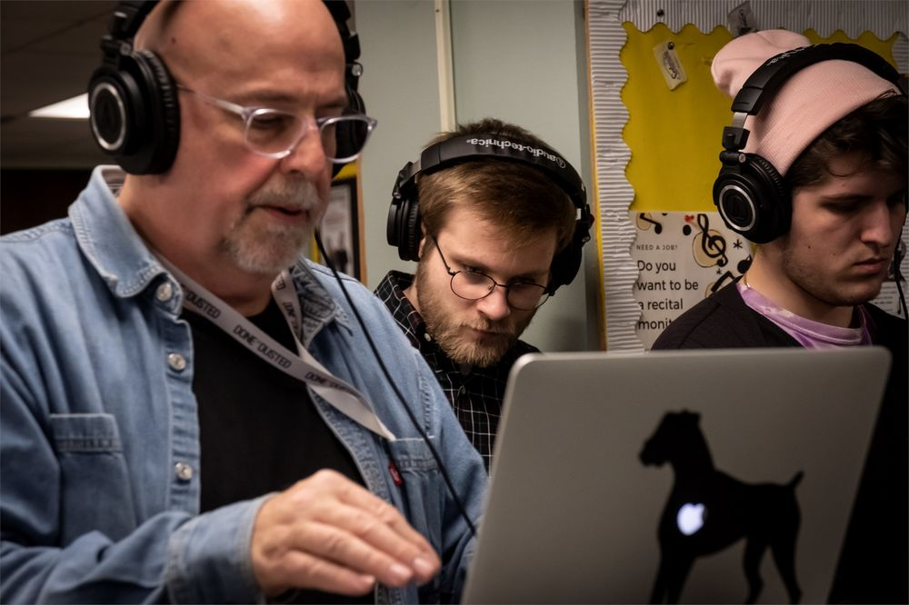 A professor with headphones works on a computer while two students also wearing headphones work alongside him.