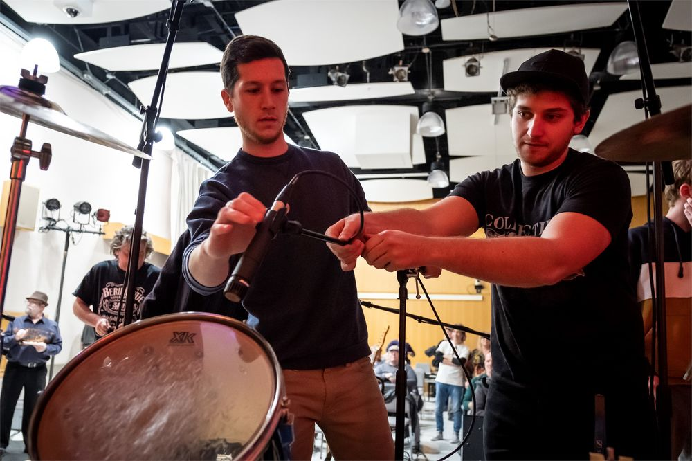 Two students set up microphones for a music recording session.