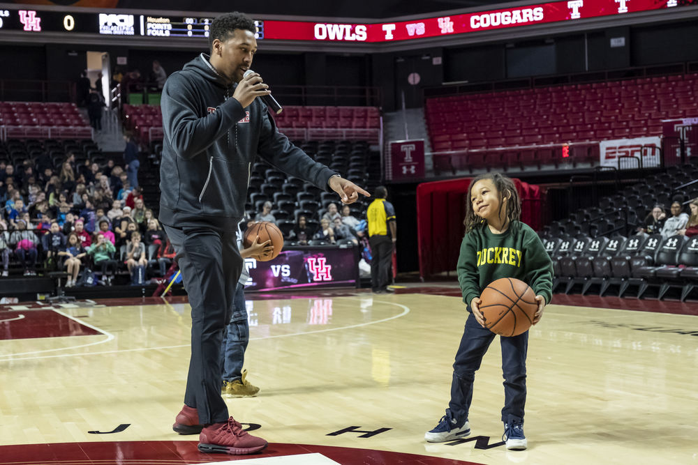 A Temple basketball player and child on the court.
