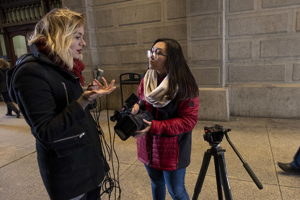 A student reporter talks with a source on the street.