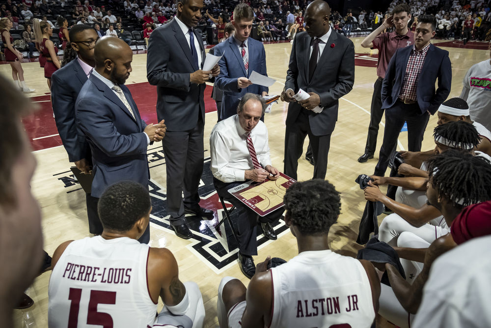A group of men in suits and the coach speak to Temple basketball players on the court.