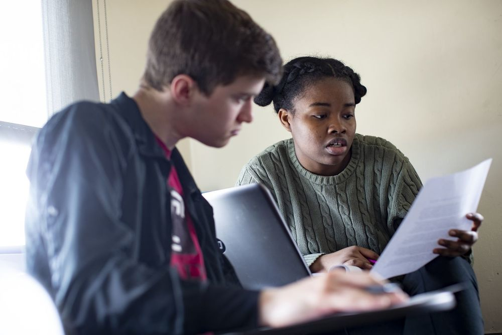 Two students read a paper together.