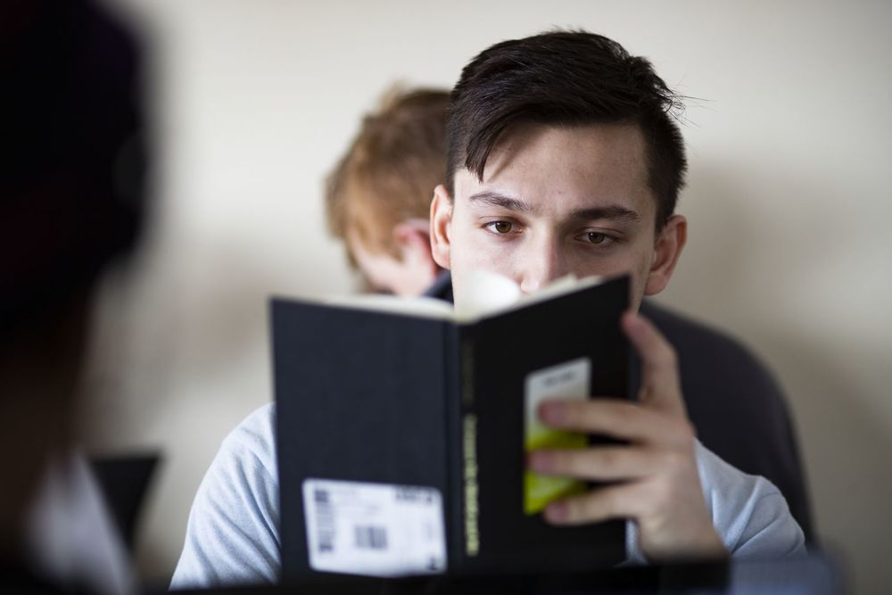 A male student's face is obscured by the book he is reading.
