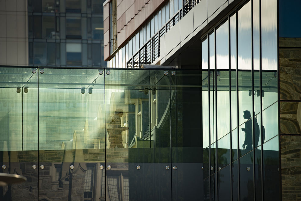 A student walks across the glass bridge between buildings on Temple's main campus.