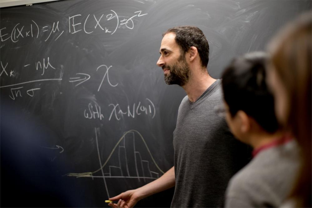 Temple professor working through complex math problem with students