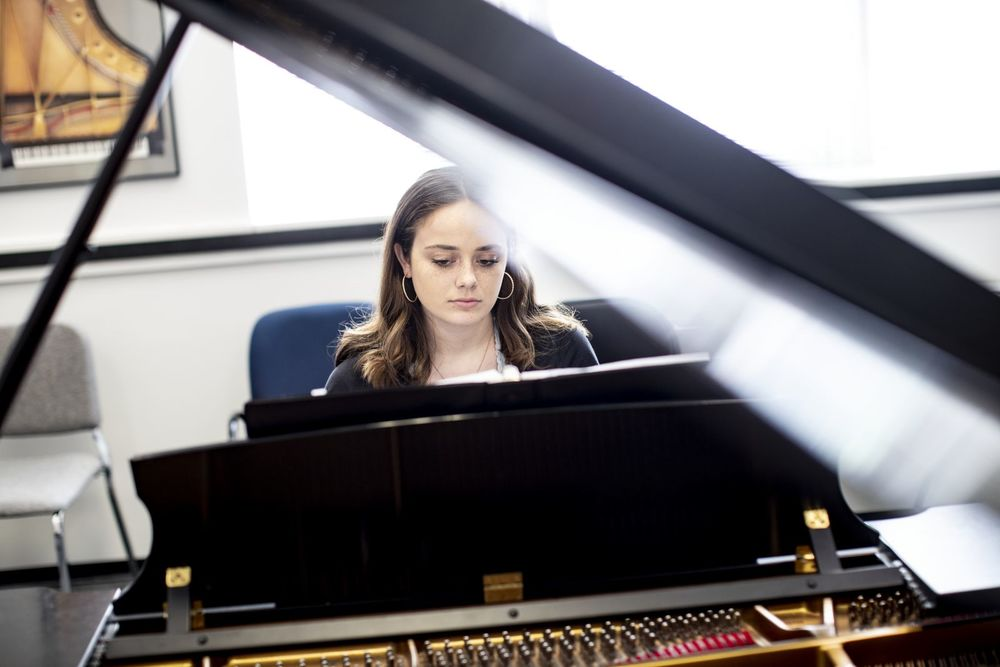 A Boyer College of Music and Dance student plays the piano in a rehearsal room on Temple's campus.