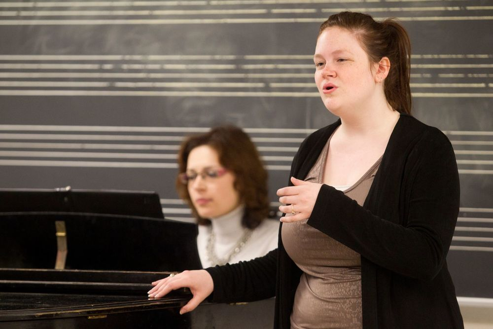A Boyer College of Music and Dance student sings while a woman plays the piano.