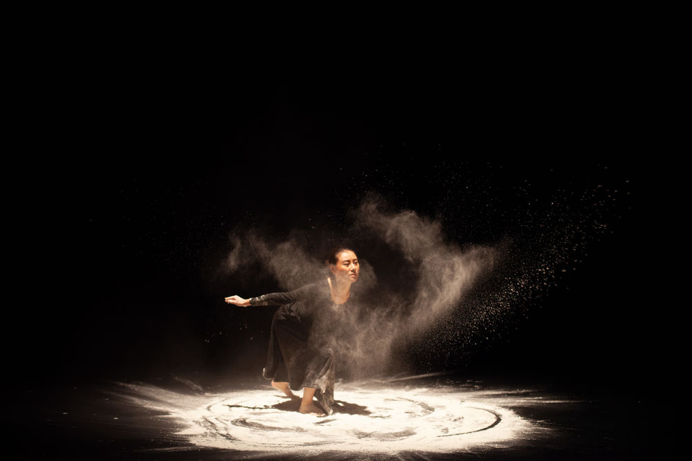 A dancer performs on stage, swirling in sand, creating a unique visual effect.