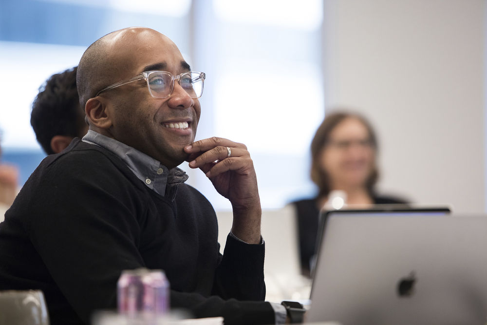 A Temple professor smiles during a student presentation.