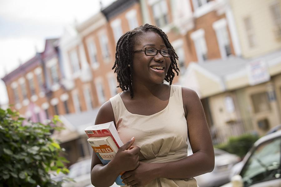Higher education university student holding stack of books