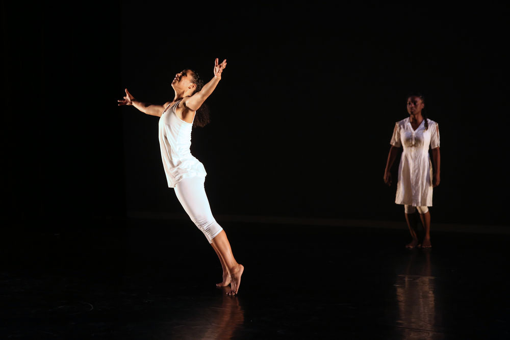 A dancer leaps on stage, with another standing behind her.