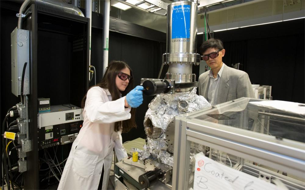 Temple faculty and students using complex machinery in a CST lab