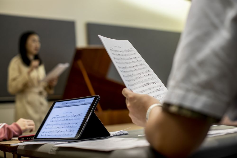Music students looking at sheet music both on paper and on a computer while a professor lectures at the front of the classroom.