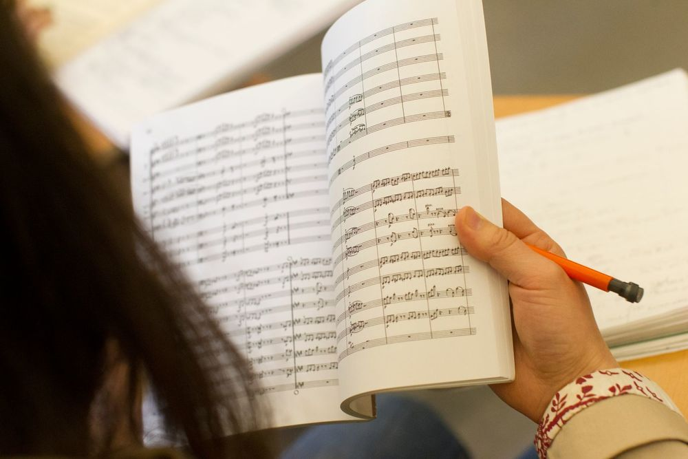 A student reads a book of sheet music.