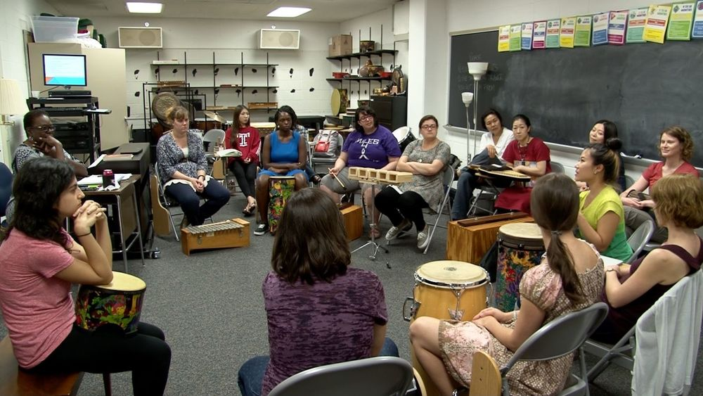 Music Therapy Jazz students sit in a circle in a classroom with different kinds of percussion instruments in front of them.