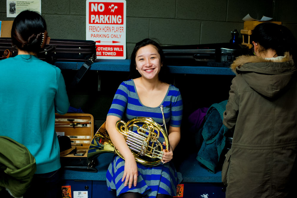 A student sits and smiles while holding her french horn.