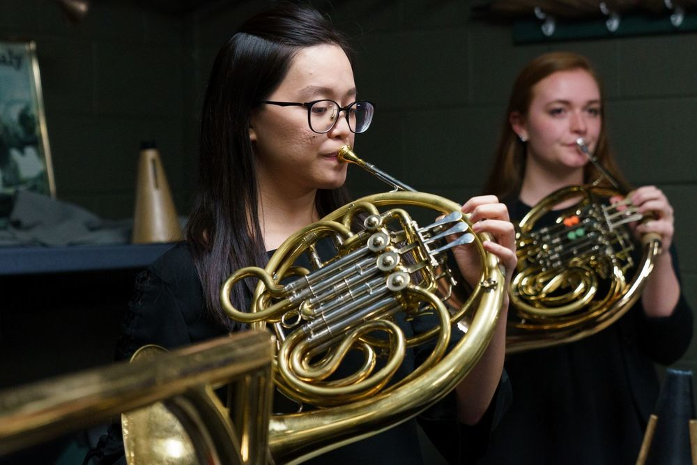 Two Temple University Boyer College of Music and Dance students play the french horn.