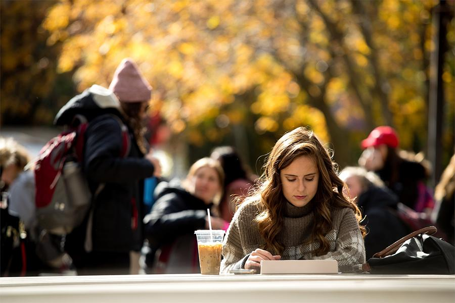 College student studying outdoors at a picnic table