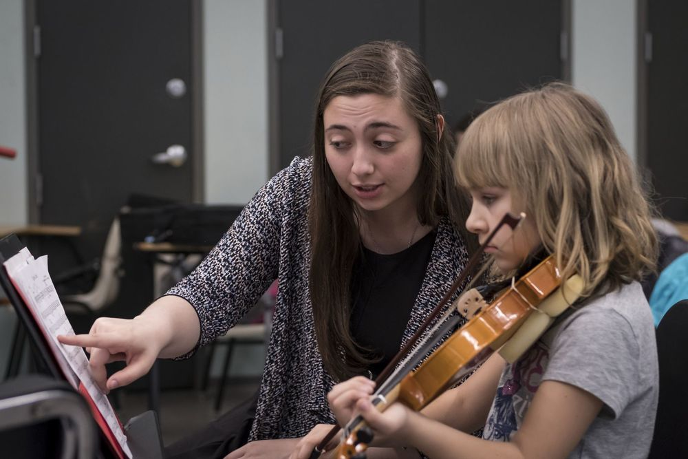 A Temple music student works with an elementary school student during a violin lesson.