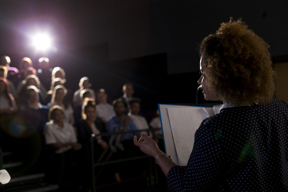 An actress holding a script is reciting lines in front of an audience.