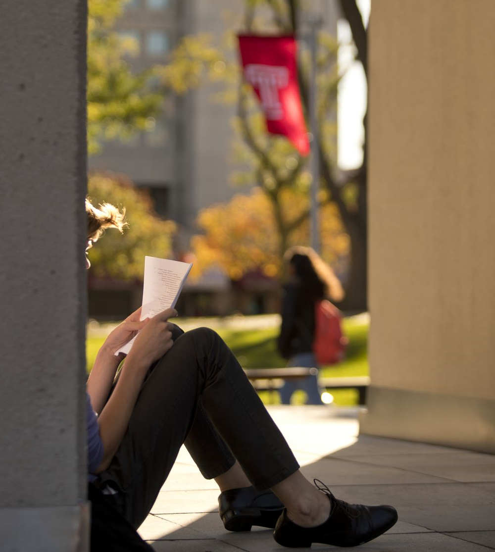 A student sits in the shade on a sunny afternoon, reading a packet of papers